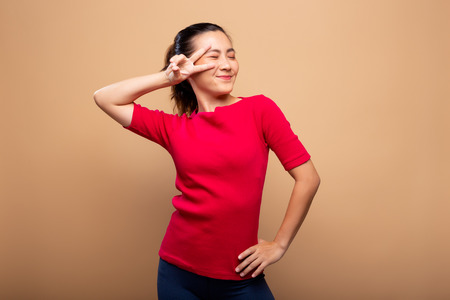 Portrait of happy woman smile and showing peace sign with fingers isolated over background