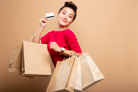 Portrait of woman holding shopping bags and credit card isolated over background