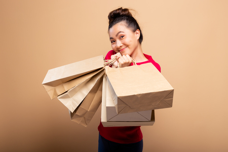 Portrait of woman holding shopping bags isolated over background