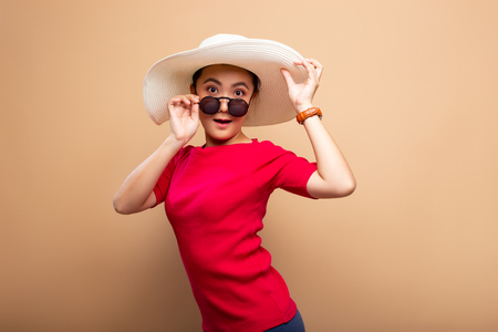 Portrait woman wearing big hat isolated on brown beige background Фото со стока