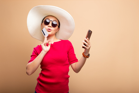 Woman wearing hat and sunglasses use smart phone and credit card isolated on background