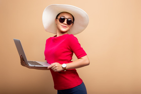 Woman wearing hat and sunglasses use laptop isolated on background