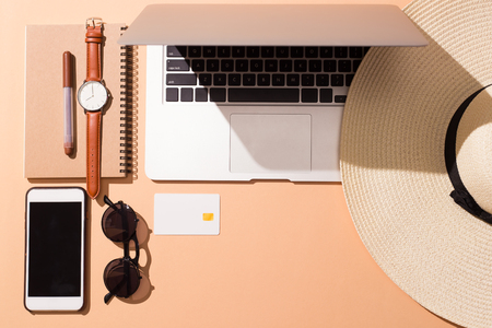 Laptop and smart phone with items for vacation time over isolated Reklamní fotografie