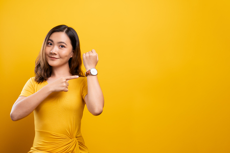 Happy woman holding hand with wrist watch isolated on a yellow background