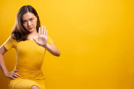 Woman making stop sign with hand on isolated yellow background