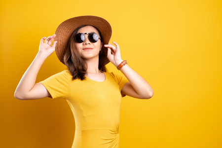 Portretvrouw die zonnebril en hoed draagt die over gele achtergrond wordt geïsoleerd Stockfoto