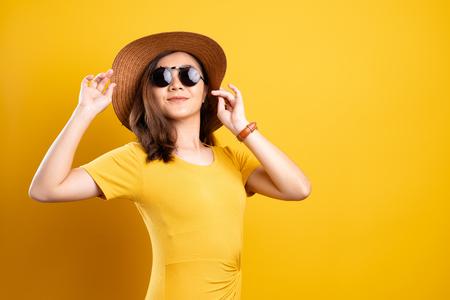 Ritratto di donna che indossa occhiali da sole e cappello isolato su sfondo giallo Archivio Fotografico