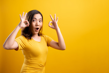 Happy woman showing OK gesture isolated on yellow background Фото со стока
