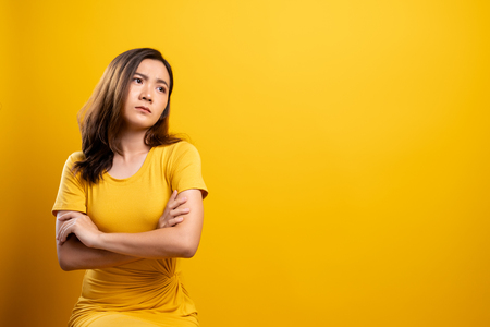 Sad woman isolated over yellow background