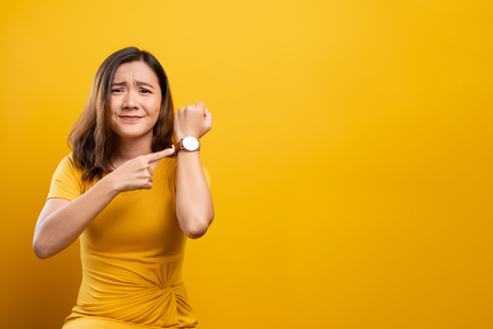 Shocked woman holding hand with wrist watch isolated on a yellow background