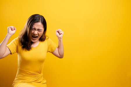 Angry woman screaming isolated over yellow background