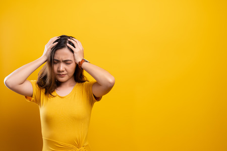 Woman has headache isolated over yellow background