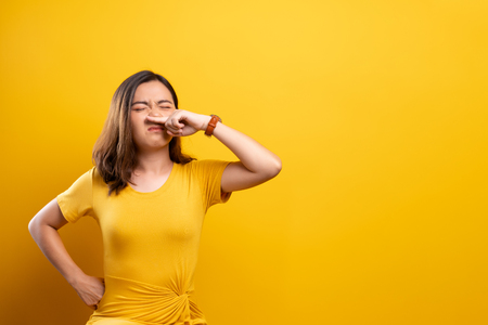 Woman sneezing isolated over yellow background