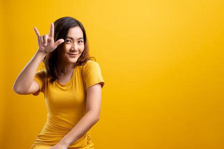 Woman in love showing heart isolated over yellow background