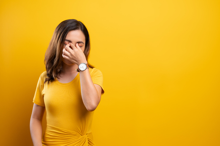 Woman has eyes pain isolated over yellow background