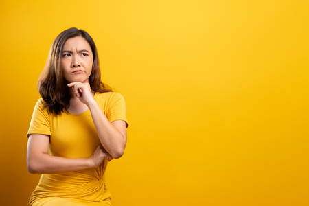 Woman feel confused isolated over yellow background Stock Photo