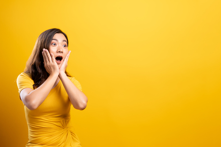 Retrato de mujer emocionada aislada sobre fondo amarillo Foto de archivo