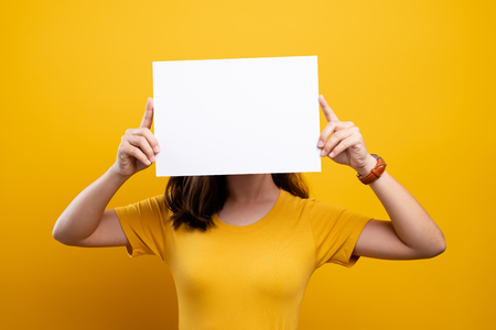 Woman covering face with blank paper