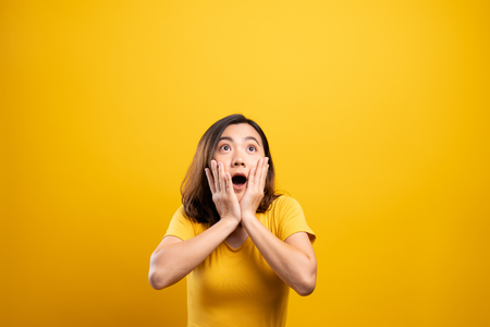 Portrait of excited woman isolated over yellow background