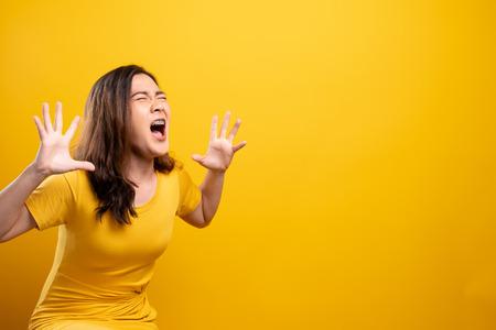 Donna arrabbiata che urla isolata su sfondo giallo Archivio Fotografico