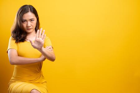 Mujer haciendo señal de stop con la mano sobre fondo amarillo aislado