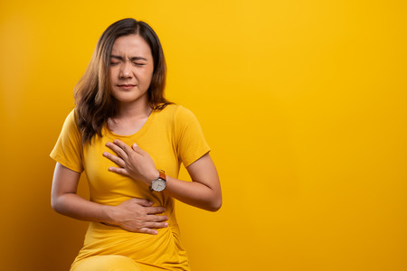 Woman has stomachache isolated over yellow background Foto de archivo