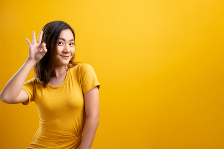 Happy woman showing OK gesture isolated on yellow background Stok Fotoğraf