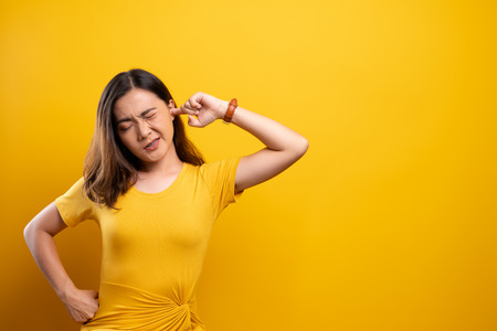 Woman putting a finger into her ear 스톡 콘텐츠
