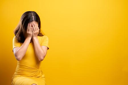 Mujer triste aislada sobre fondo amarillo Foto de archivo