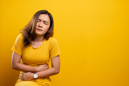 Woman has stomachache isolated over yellow background 版權商用圖片