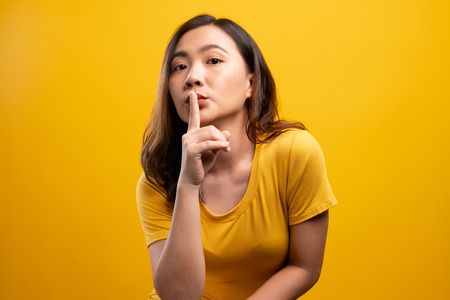 Woman show a quiet sign isolated over yellow background