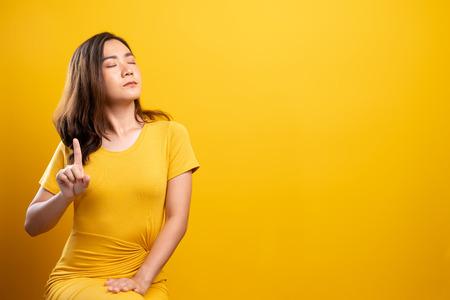 Donna che fa il segnale di stop con la mano su sfondo giallo isolato