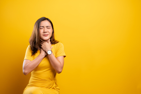 Woman has sore throat isolated over yellow background Standard-Bild