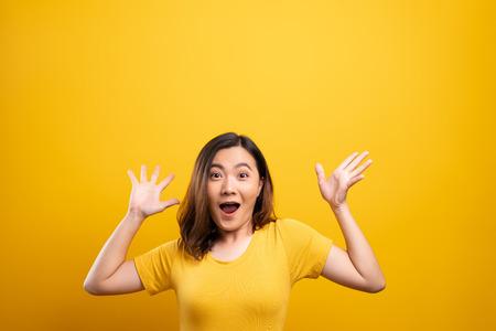 La donna felice fa un gesto vincente isolato su sfondo giallo Archivio Fotografico