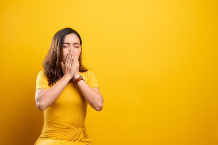 Woman has sore throat isolated over yellow background Stock Photo