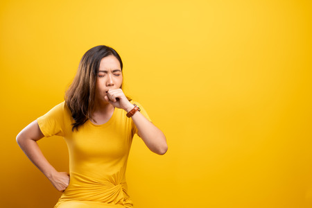 Woman has sore throat isolated over yellow background Imagens