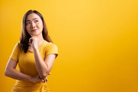 Mujer feliz pensando y de pie aislado sobre fondo amarillo Foto de archivo