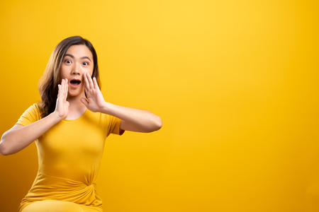 Woman make gossip gesture isolated over yellow background