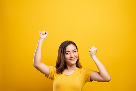 Happy woman make winning gesture isolated over yellow background