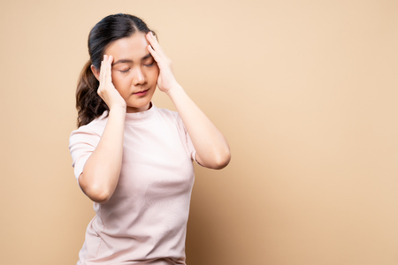 Woman has headache isolated over beige brown