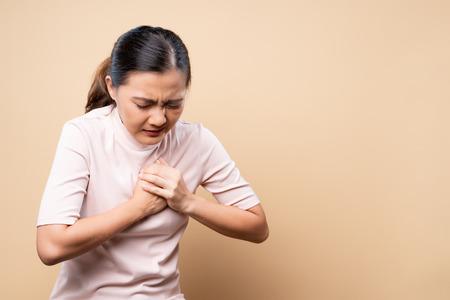 La mujer tiene dolor en el pecho aislado sobre marrón beige Foto de archivo