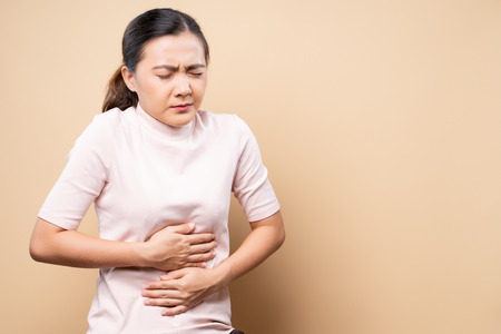 Woman has stomachache isolated over beige brown