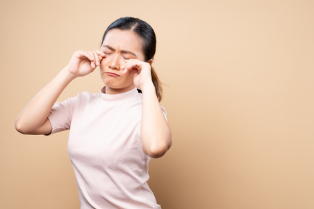 Sad woman crying and standing isolated on beige brown background 스톡 콘텐츠