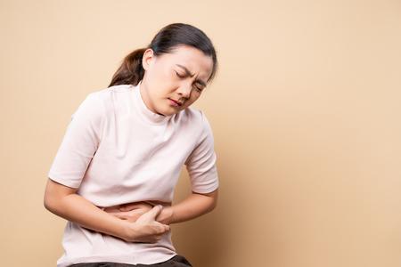 La femme a le mal d'estomac d'isolement au-dessus du brun beige