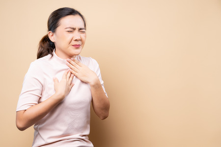 Woman has sore throat isolated over beige brown Stock Photo