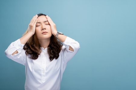 Woman has headache isolated over blue background