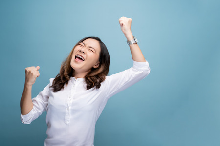 Happy woman make winning gesture isolated over blue background