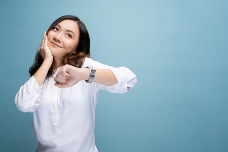 Happy woman holding hand with wrist watch isolated on a blue background 스톡 콘텐츠