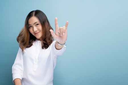 Woman in love showing love sign isolated over blue background Stock Photo