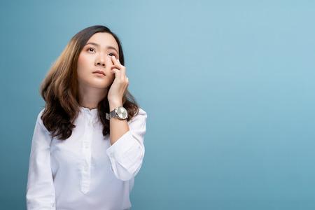 Frau hat Augenschmerzen auf blauem Hintergrund isoliert